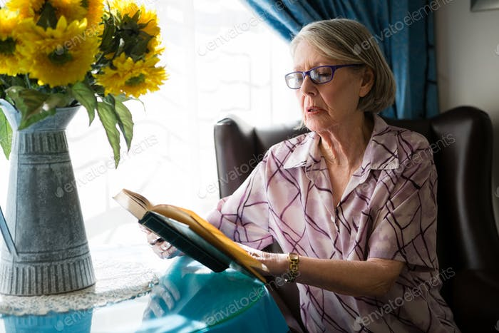 Senior woman reading book while sitting in retirement home