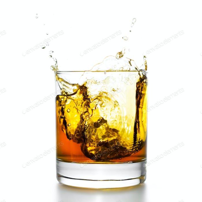 Whiskyglas mit Spritzern, isoliert auf weiß