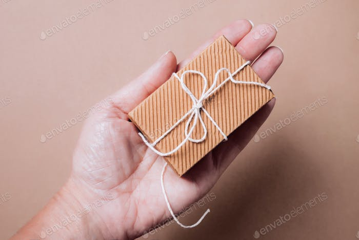 Cute small corrugated gift box with natural string in female hand