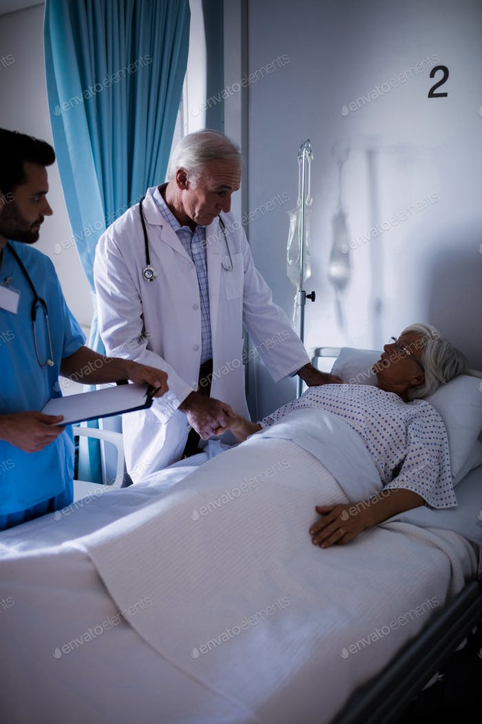 Doctors comforting senior patient on bed