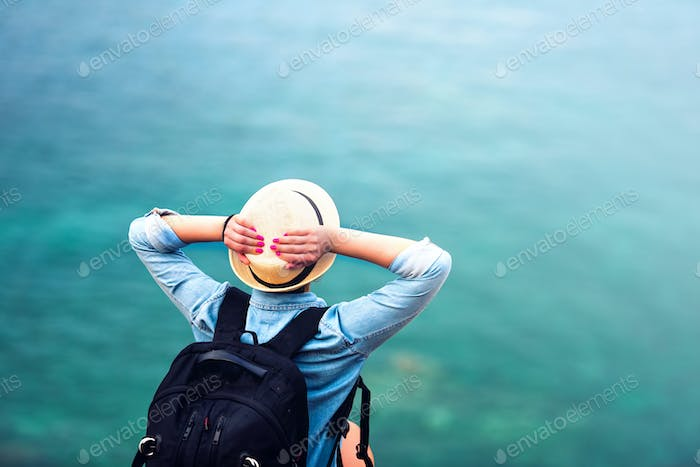 woman on summer vacation, hiking on coastline and staring at sea wearing hat and backpack.