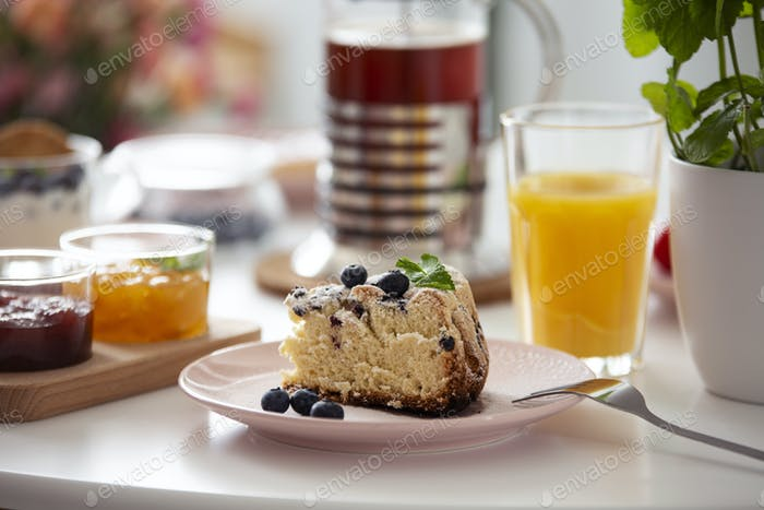 Close-up on cake on plate on a table with orange juice during br