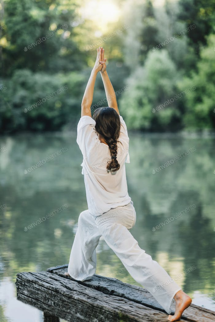 Yoga by the Lake – Young woman practicing Warrior 1 Pose