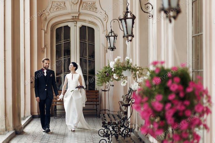 Невеста и стильный жених ходьба держась за руки