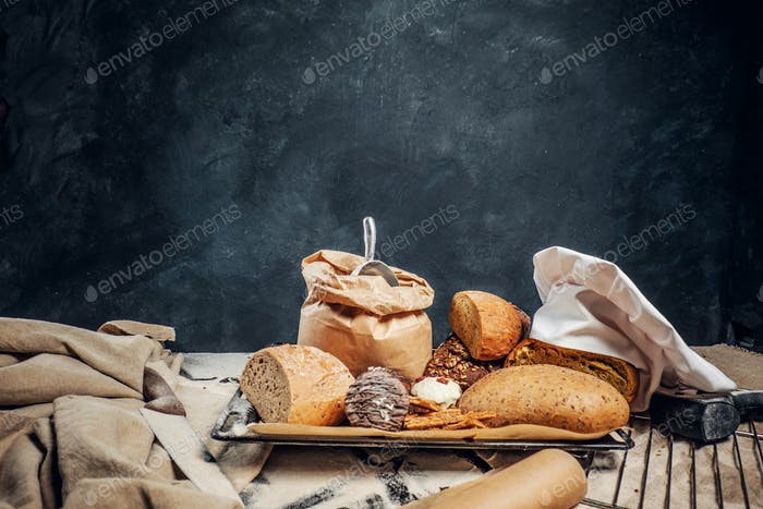 Freshly bread baguettes and muffins on a wooden table on a dark textured wall.