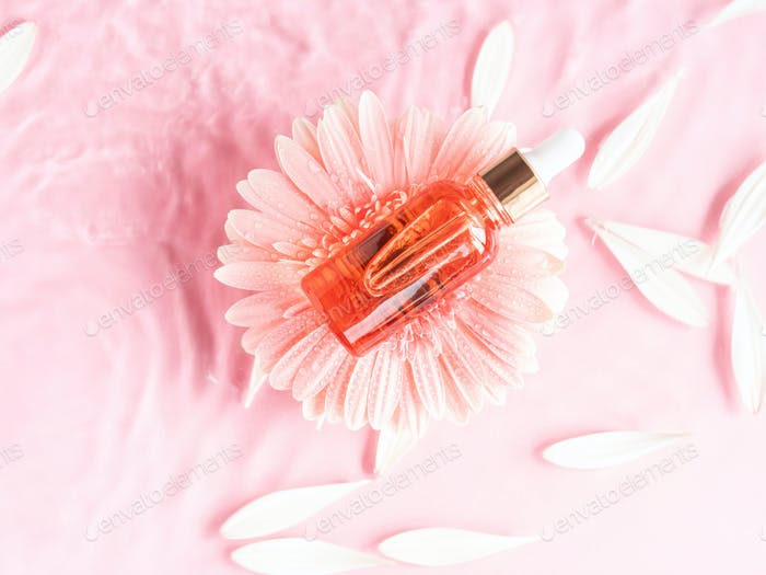 Cosmetic beauty serum oil acid bottle product on pink background in water with pink daisy