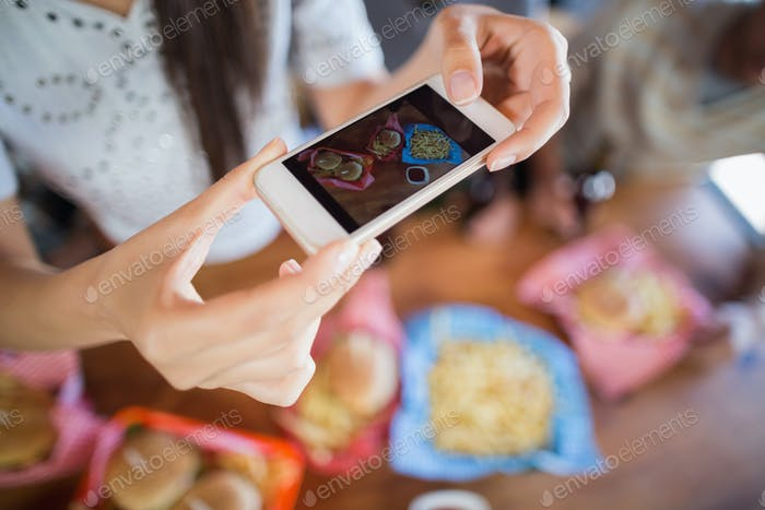Woman photographing food through mobile in restaurant