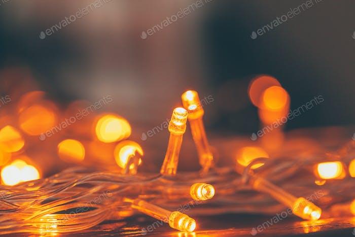 Warm light illuminated garland close up on dark background