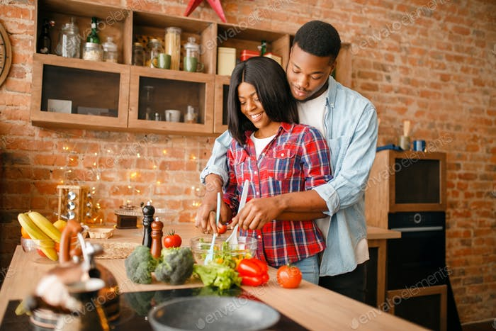 Black love couple cooking together on the kitchen