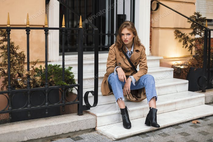 Young attractive woman in trench coat and jeans thoughtfully loo