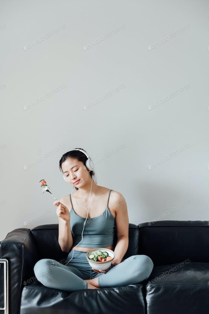Junge asiatische Frau essen Salat nach dem Training