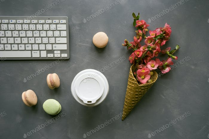 Office desk table with computer keyboard, cup of coffee and flow