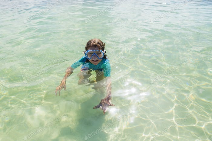 5 Jahre alter Junge im Wasser hält einen Sternfisch, Grand Cayman Island
