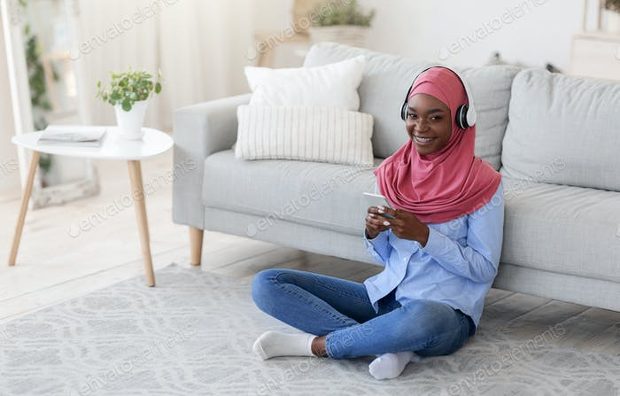 Stay At Home. Smiling Black Muslim Woman Relaxing With Smartphone And Headphones