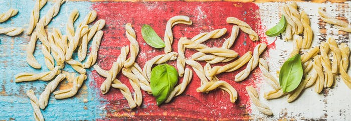 Homemade uncooked pasta casarecce with flour and green basil leaves