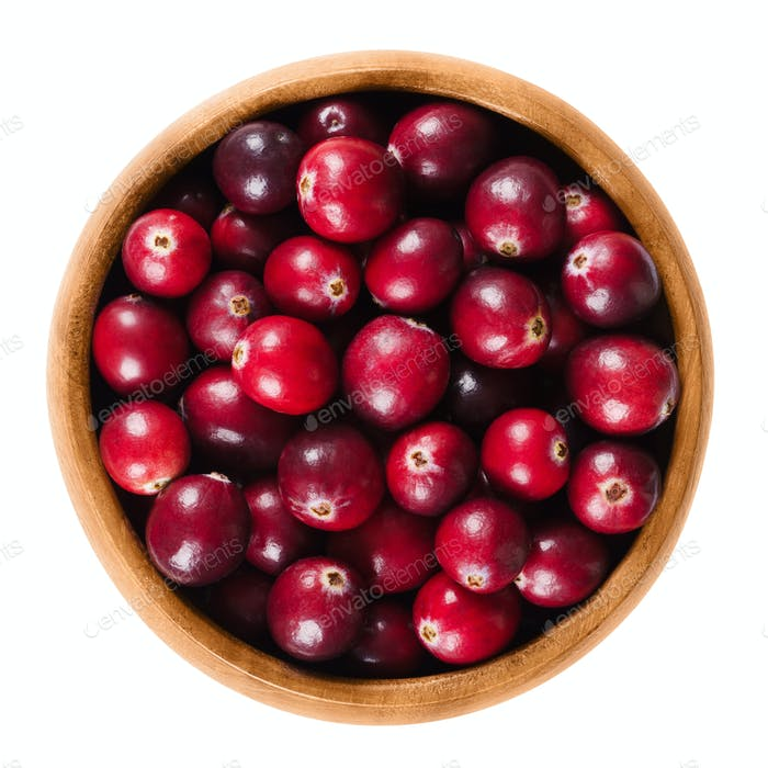 Fresh cranberries in wooden bowl over white