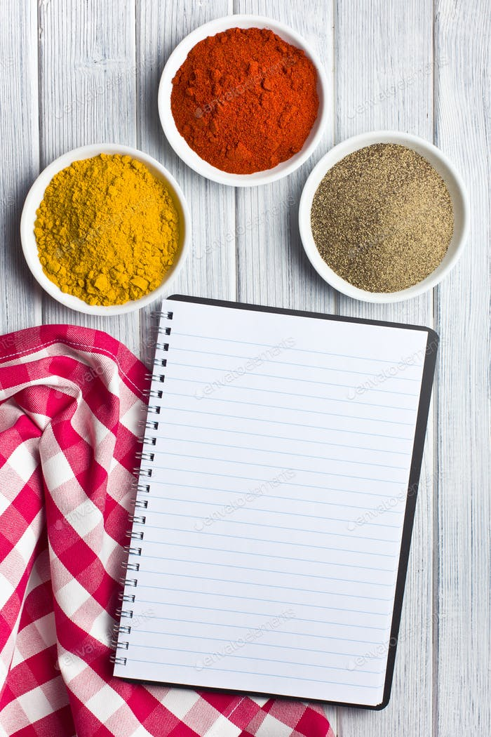 various colored spices with blank recipe book