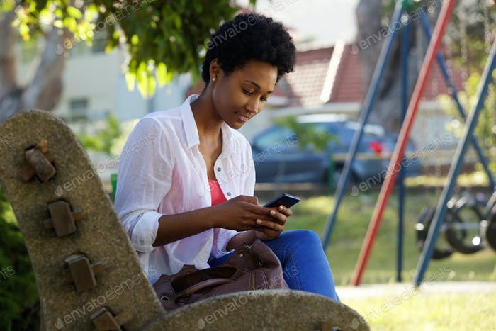 Young woman sitting on a bench sending text message