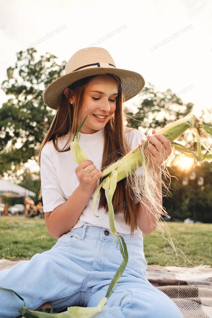 Young attractive brown haired girl in straw hat happily cleaning corn on picnic in city park