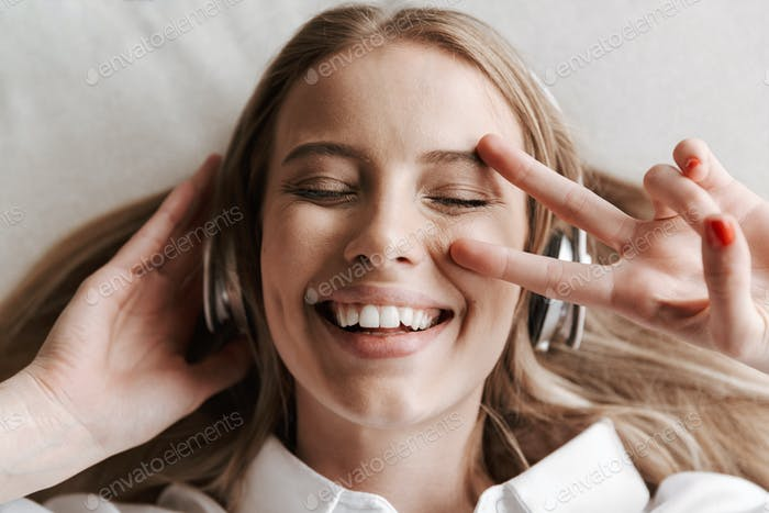 Top view of excited young woman in headphones