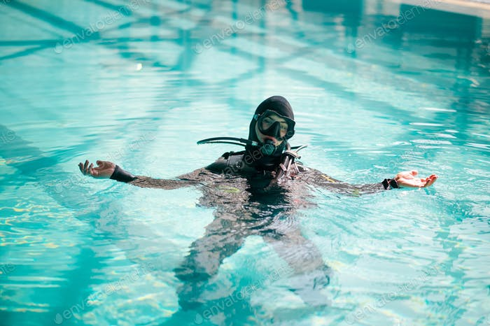 Male diver in scuba gear poses in pool, diving