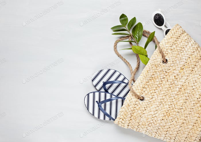 Tropical beach accessories top view with straw summer bag and flip flops