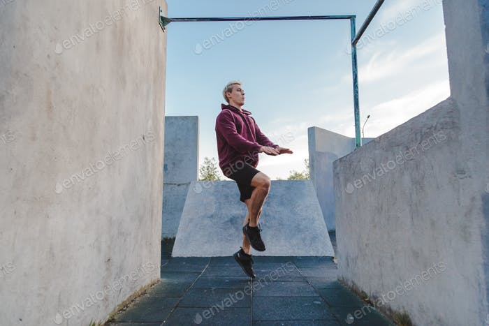 Young sportsman running on the spot outdoor for warming up before parkour training