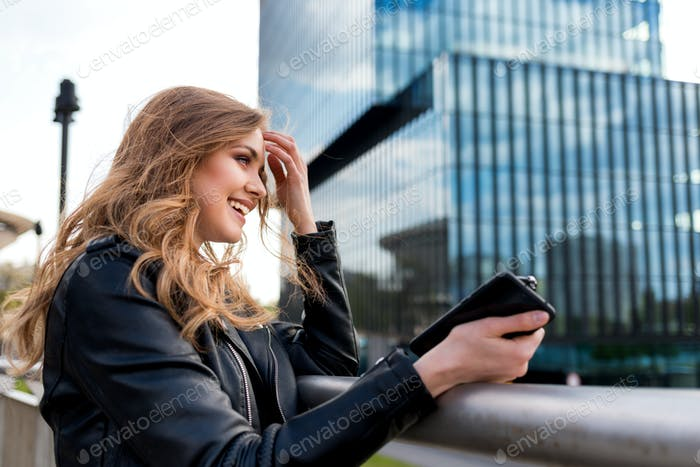 Beautiful smiling woman looking at modern office buildings in modern city
