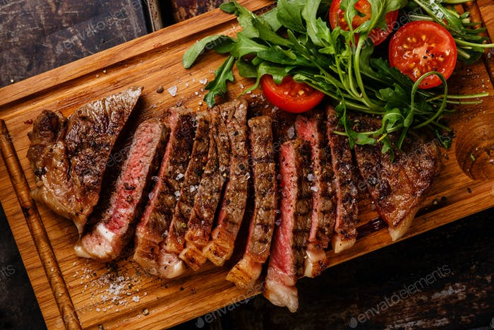 Sliced grilled beef barbecue Striploin steak and salad