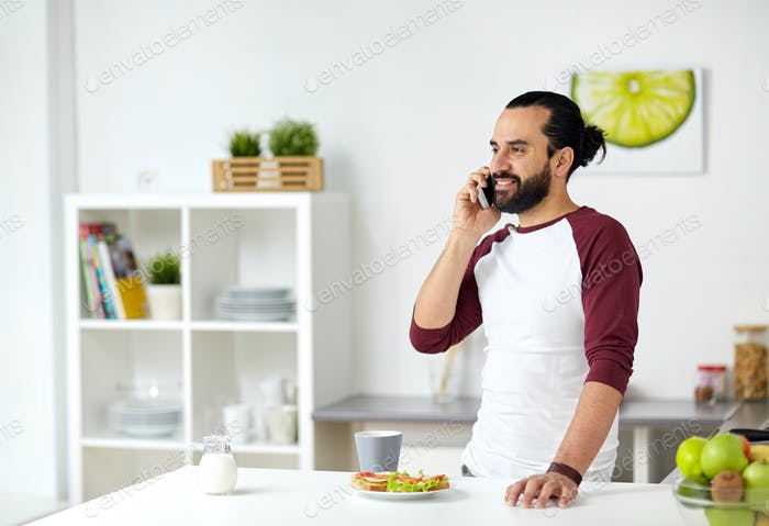 man calling on smartphone and eating at home