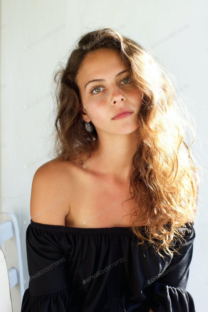 Beautiful young woman with curly hair staring