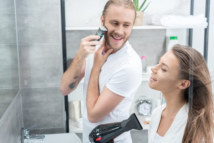 Handsome young man shaving beard with electric razor and smiling woman drying hair with hair dryer