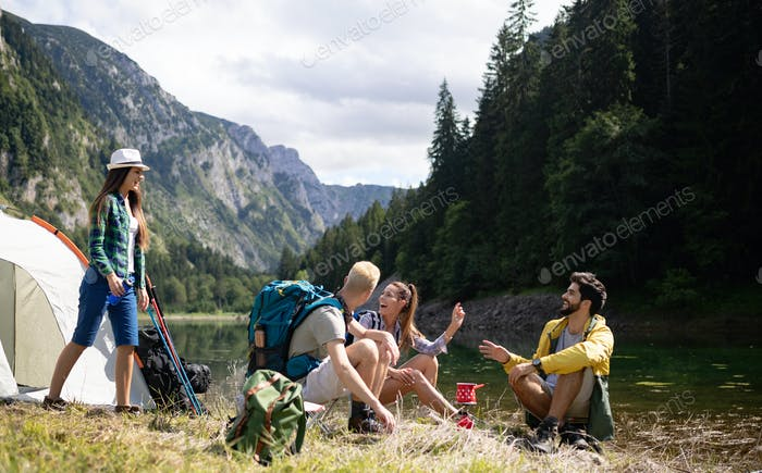 Smiling young people enjoying nature beside tents and talking outdoor