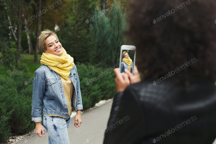 Happy girls with smartphone outdoors in the park