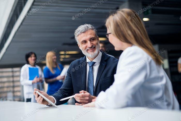 Arzt im Gespräch mit einem pharmazeutischen Vertriebsmitarbeiter