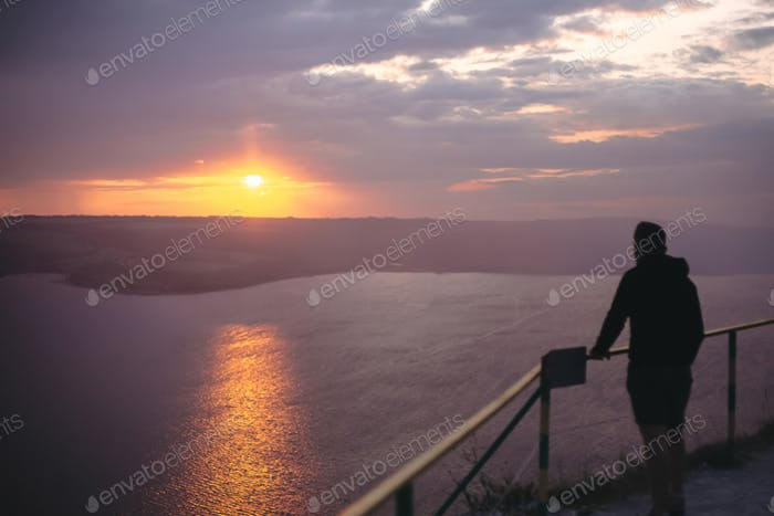 Hipster traveler standing on top of rock mountain and enjoying amazing sunset view on river