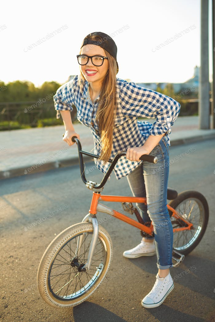Lovely young woman in a hat riding a bicycle on city background