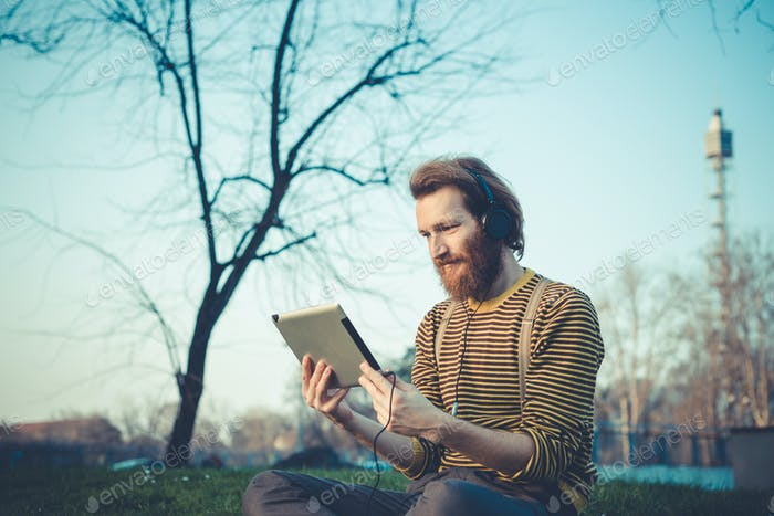 junge bärtige stilvolle schöne hipster Mann mit Tablet