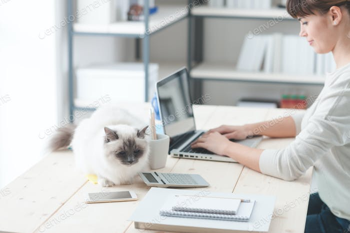 Woman working at desk with her cat
