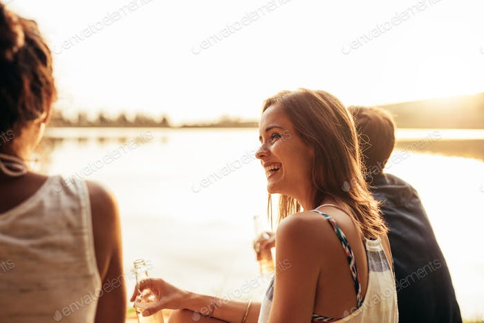 Smiling young girl sitting by a lake with friends