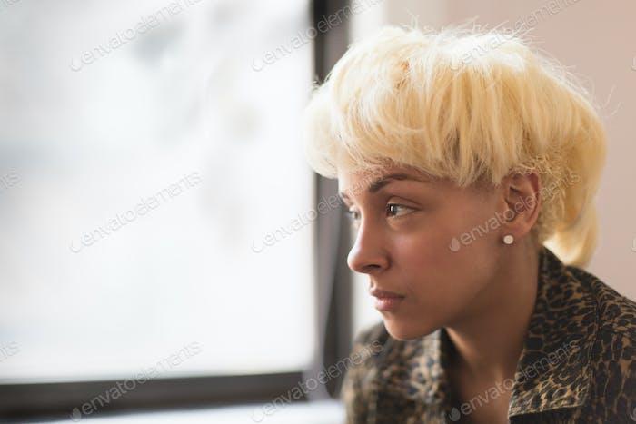 Молодая женщина с светлыми волосами смотрит в окно.