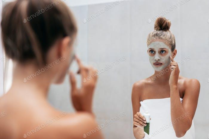 Young woman applying facial mask