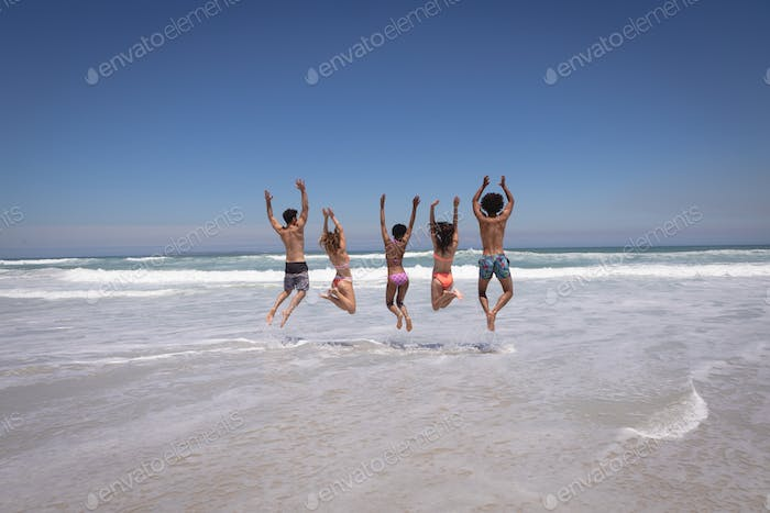Happy group of friends jumping together on beach in the sunshine against ocean waves