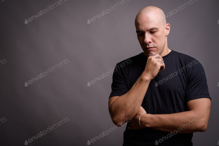 Portrait of handsome bald man against gray background