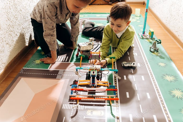 Two boys play with robots that they created from the robotic constructor on the colorful banner on
