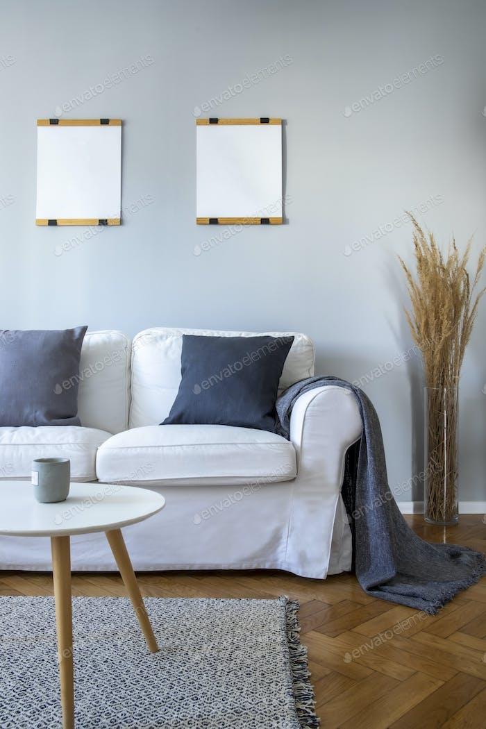 Graue Kissen und Decke auf weißem Sofa im kleinen Wohnzimmer