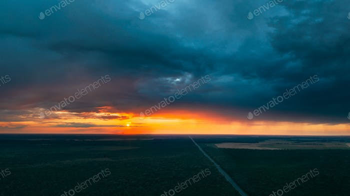 Aerial View Of Sunset Sky Above Highway Road Through Green Forest Landscape In Sunny Evening. Top