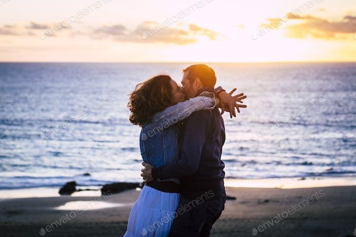 Romantic couple enjoying sunset at the beach kissing
