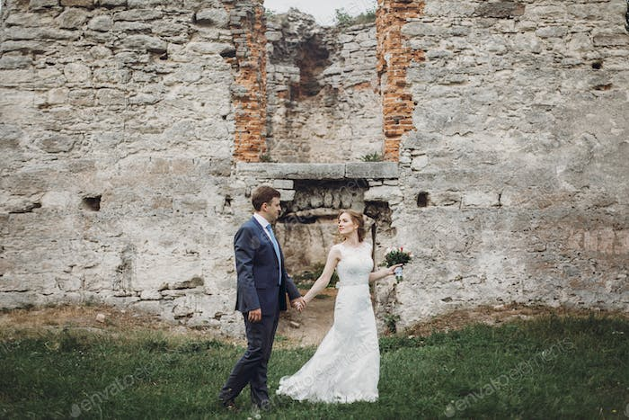 Newlywed couple posing near old castle wall, fairytale wedding at ancient castle outdoors