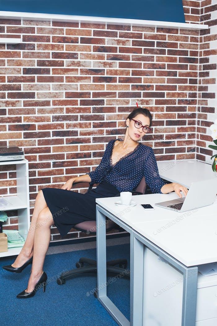 Mujer de negocios sentada en el escritorio en la oficina con portátil
